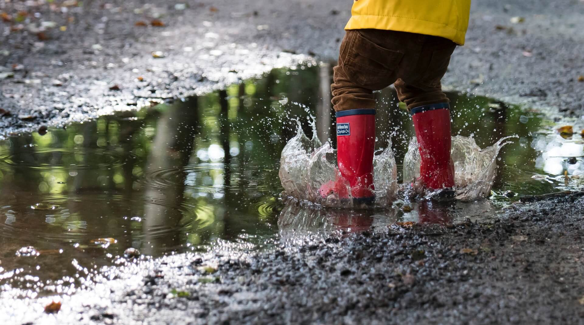 Closeup of a kid wearing red rubber boots jumping in puddles