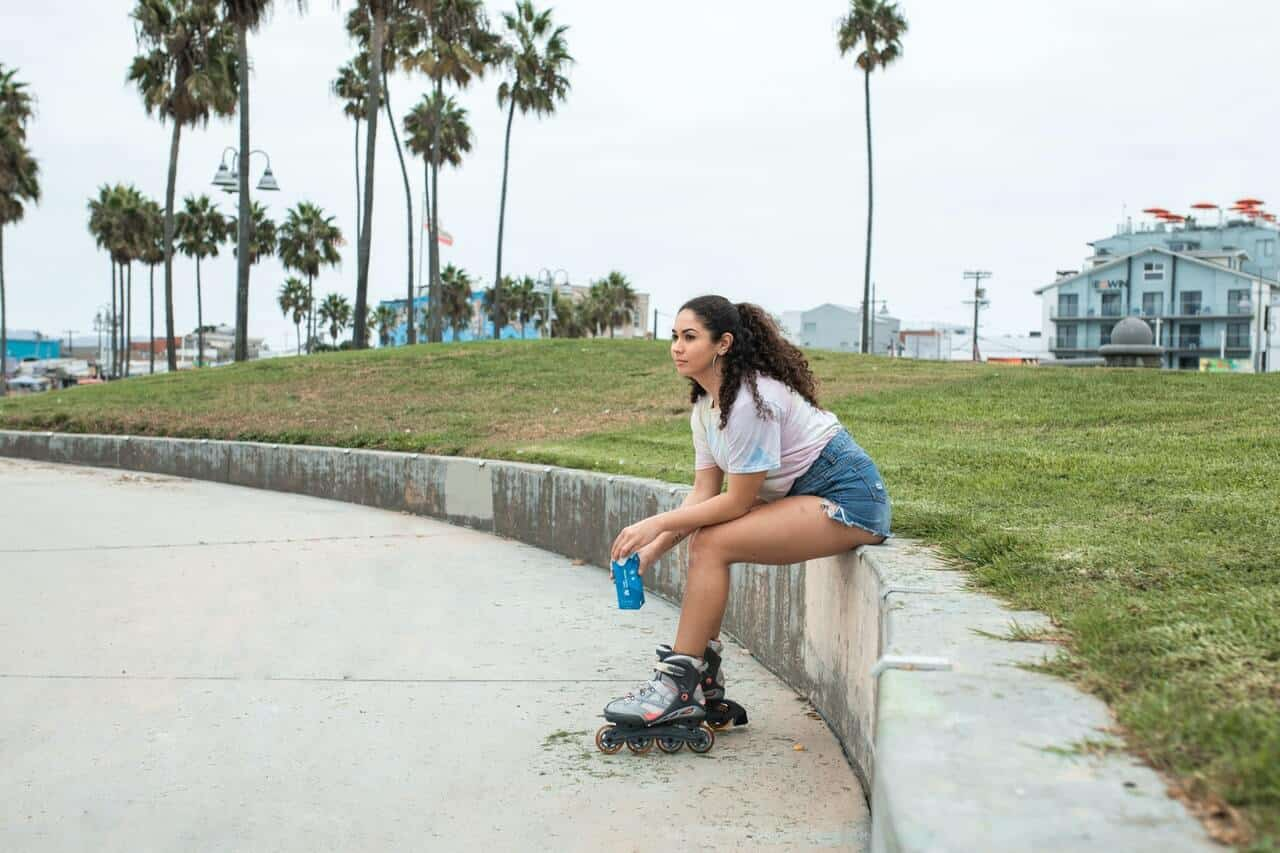 An inline skater sitting in a skater park