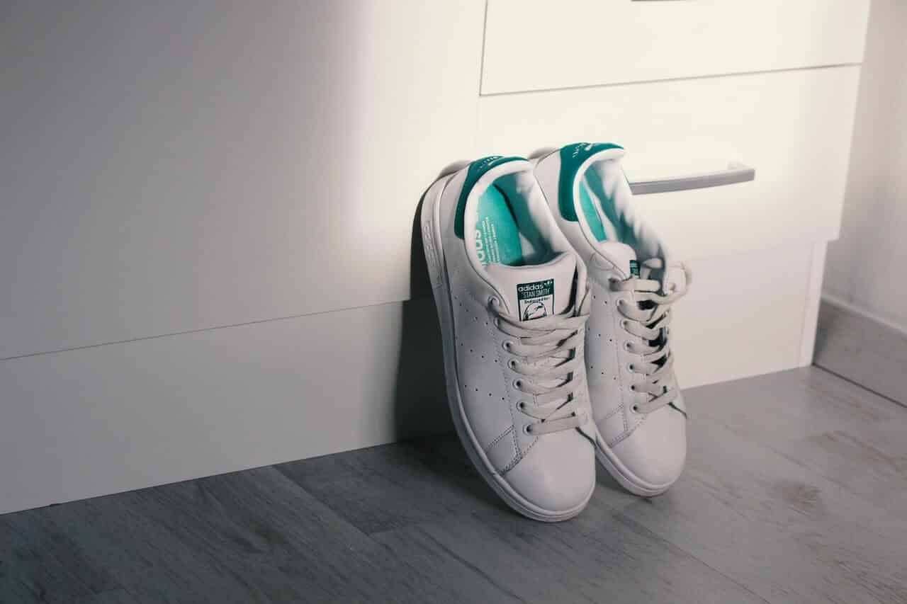Closeup of white sneakers against a white wall
