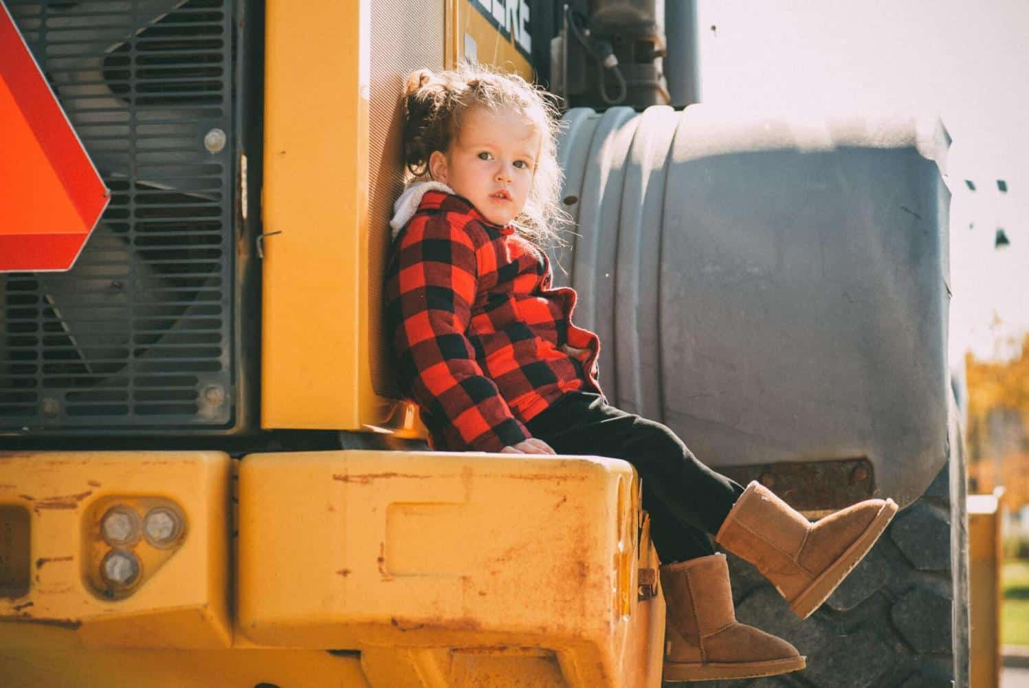 A toddler girl sitting on yellow heavy equipment.