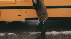 Woman standing in front of a yellow school bus wearing thigh-high boots