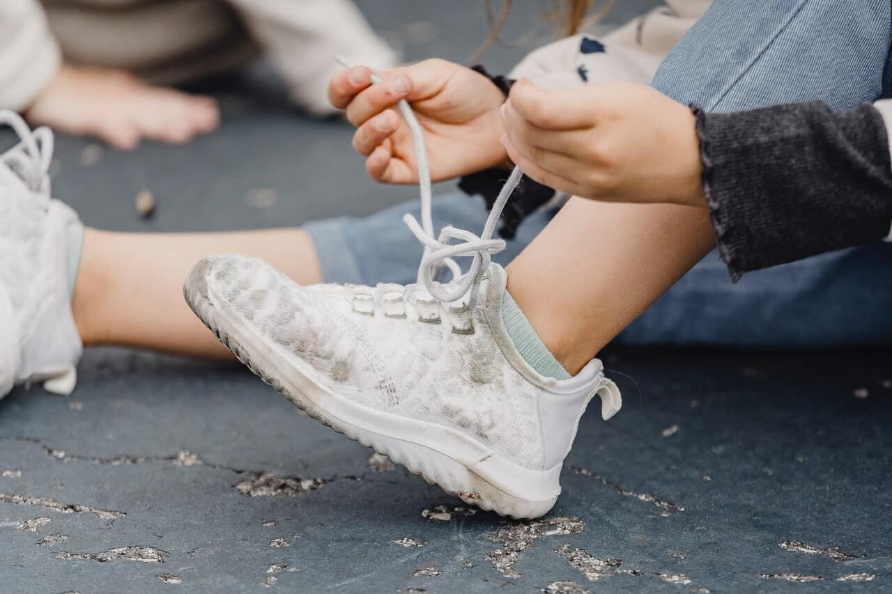 Closeup of child tying their white shoes