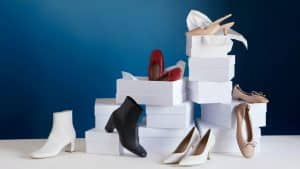 Multiple pairs of women's shoes and white shoe boxes.