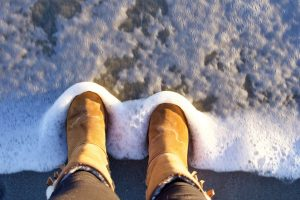 a person wearing a pair of uggs standing at a foamy shoreline