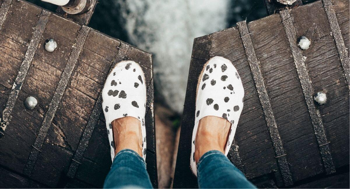 Woman standing on a wooden bridge in cow print flat shoes