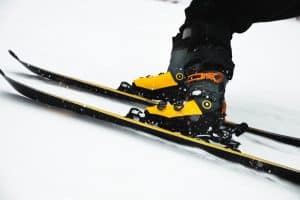 a person with black pants skiing wearing yellow ski boots