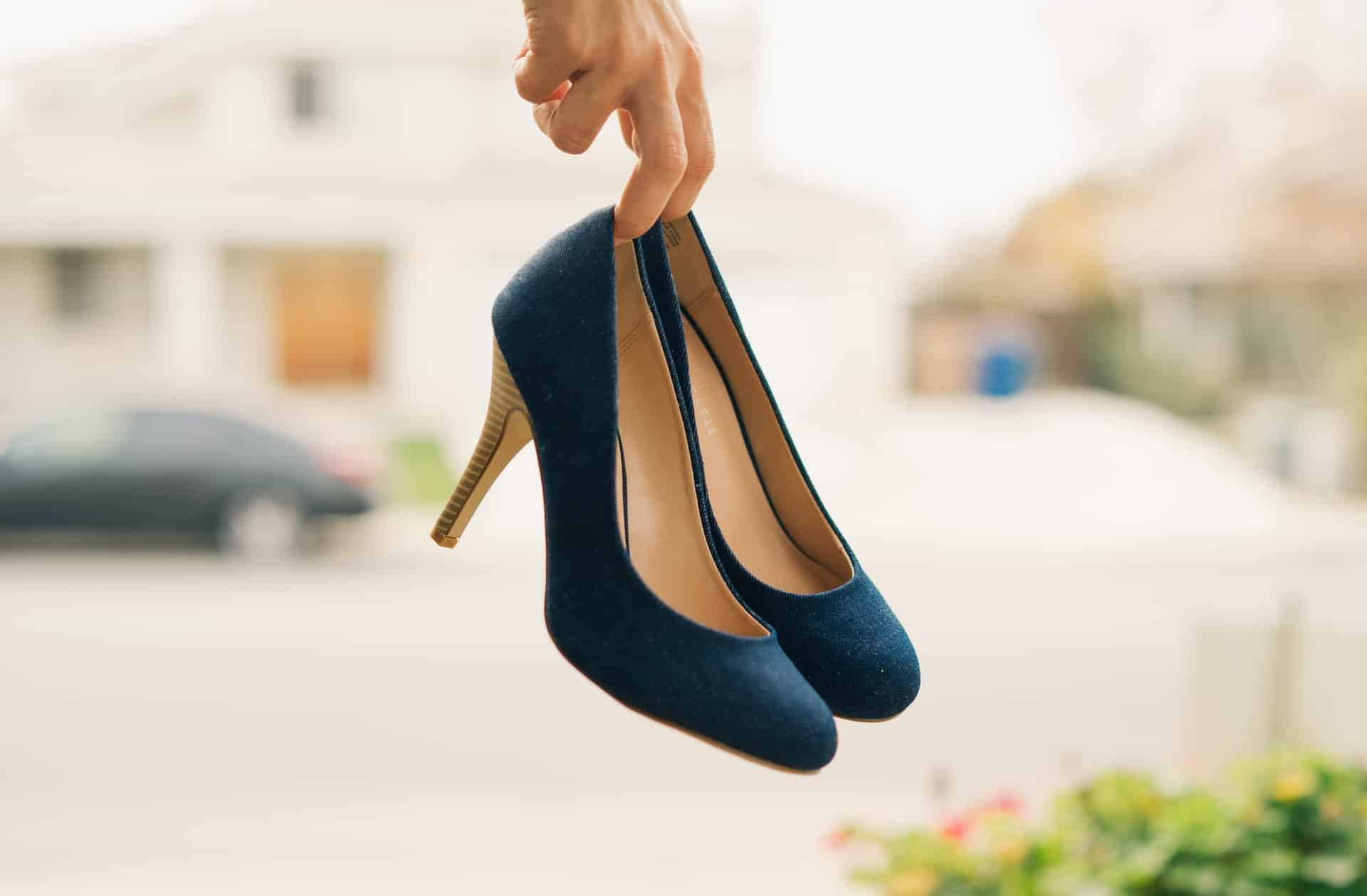 a women hold in her hands a pair of high heels