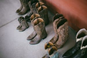 Several pairs of cowboy boots in different sizes on the floor.